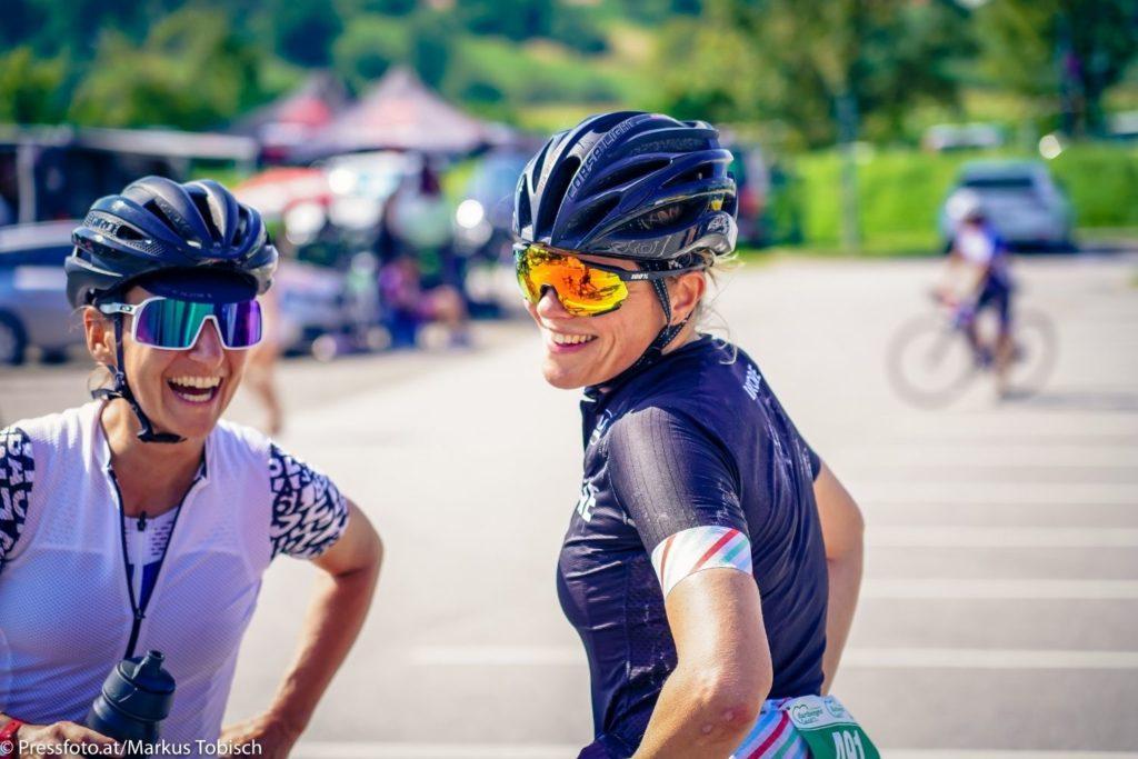 Zwei Damen lachend auf einem Platz nach dem Rennradfahren