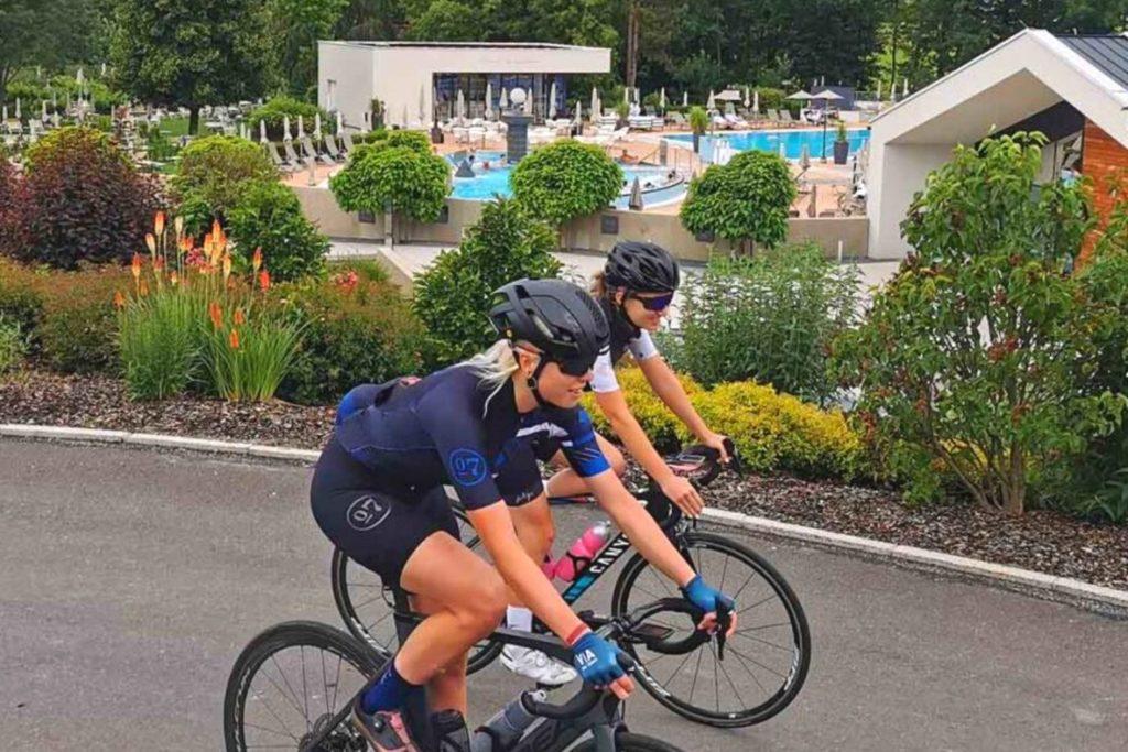Nora Turner und Anja Gleichweit fahren mit dem Rennrad an der Heiltherme Quellenhotel Bad Waltersdorf vorbei