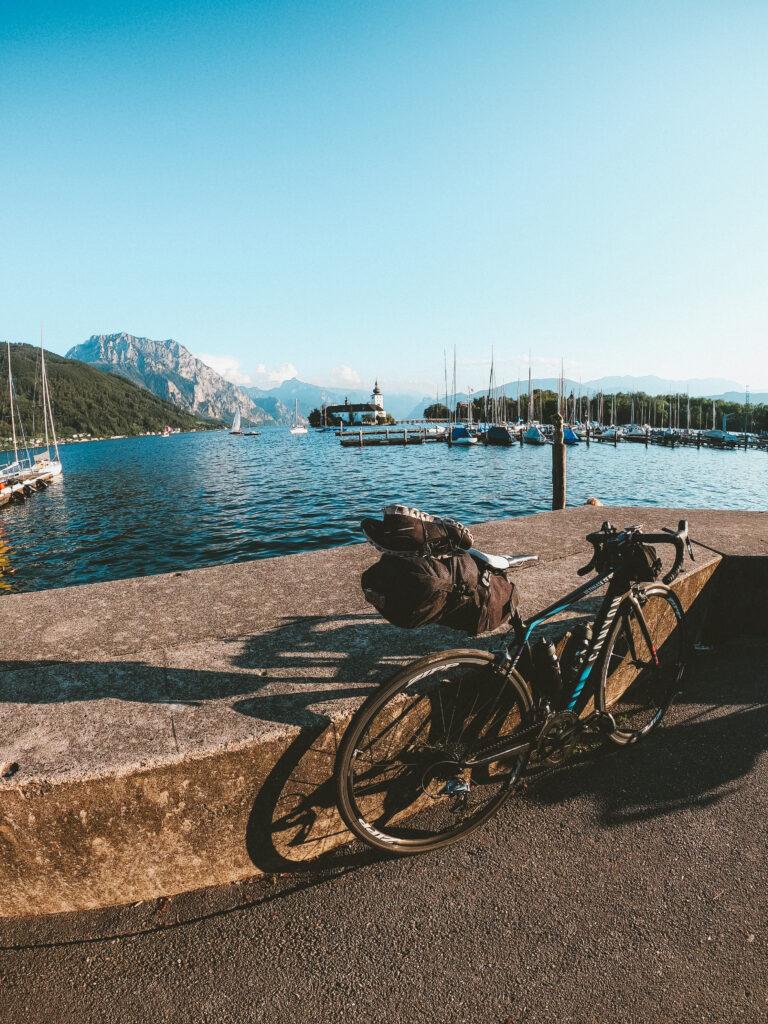 Anja's Rennrad mit Bikepacking-Ausstattung am Ufer des Traunsees mit Blick auf Schloss Ort und den Traunstein.