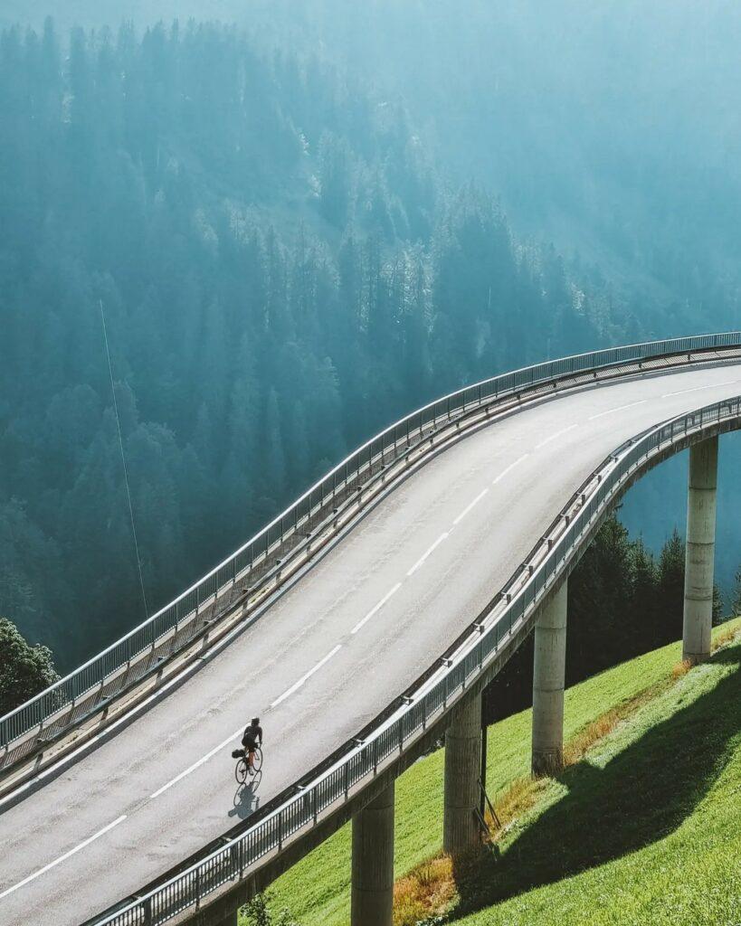 Anja mit dem Rad beim Bikepacken über eine hohe Brücke in der Nähe des Hochtannbergpasses