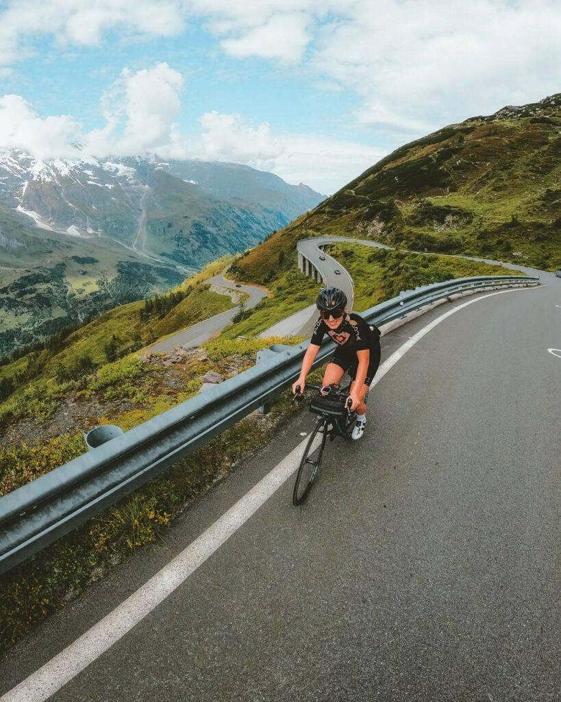 Anja mit dem Rennrad auf der Großglockner Hochalpenstraße beim Bikepacken. Im Hintergrund mehrere Kehren und das Bergpanorama.